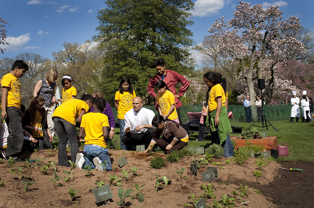 1280px-Michelle_Obama_&_Sam_Kass_show_Bancroft_students_how_to_plant_a_garden_4-9-09