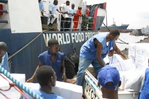 Casual Laborers with the WFP (World Food Program) load food rations onto a truck in the Free Port of Monrovia. Official USMC photo by Corporal Marcus L. Miller