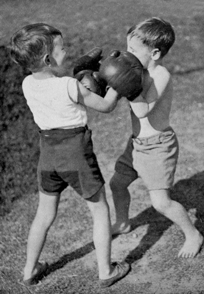 StateLibQld_2_196459_Two_young_boys_wearing_boxing_gloves_are_having_fun_sparring_outdoors,_1934